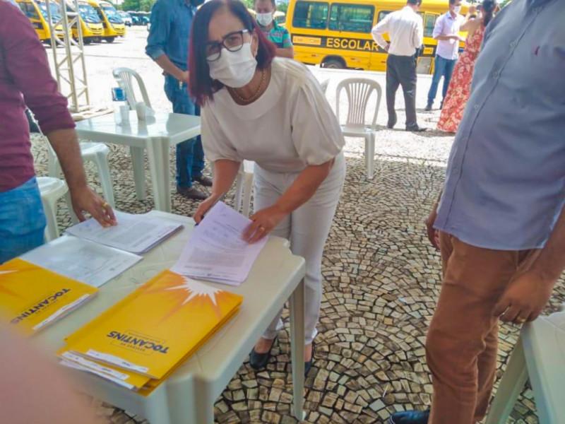 Prefeita Maria Aparecida assinando documentos para recebimento do ônibus escolar.